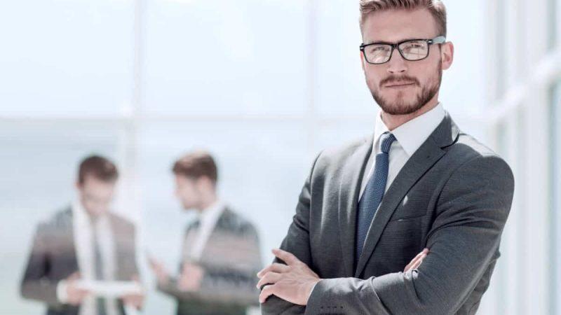 smiling businessman on blurred office background
