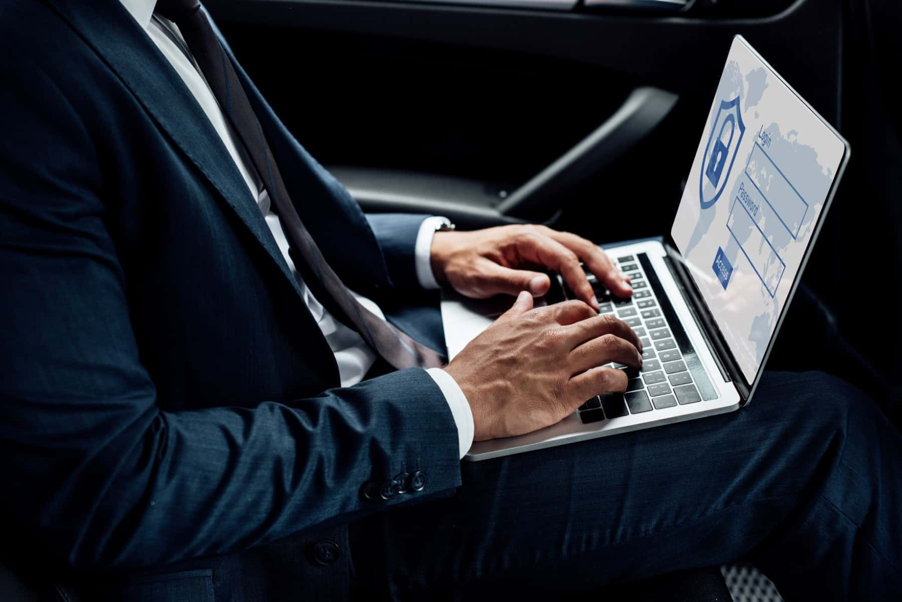 partial view of african american businessman using laptop with internet security illustration in car